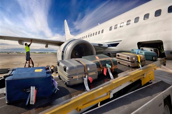 Des bagages passent en soute d'un avion