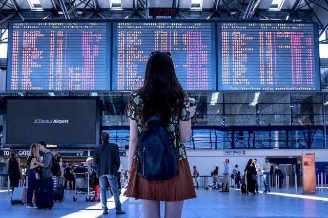 Une personne devant le tableau de départs des avions